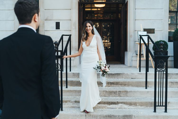 Bride in elegant dress with veil and dusky pink  wedding bouquet
