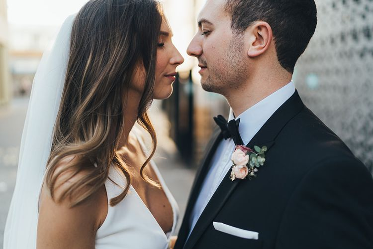 Bride and Groom embrace at city autumn wedding