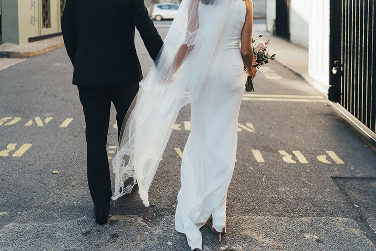 Back of Brides elegant dress with long veil walking through East London for autumn wedding celebration