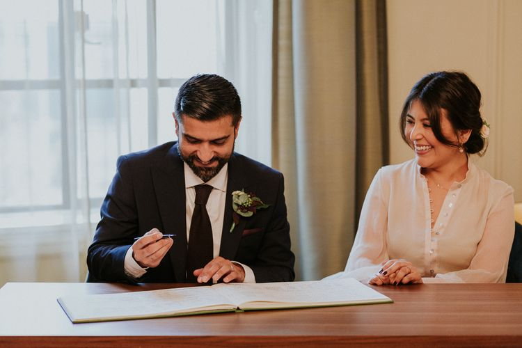 Bride and groom signing the register at intimate town hall wedding