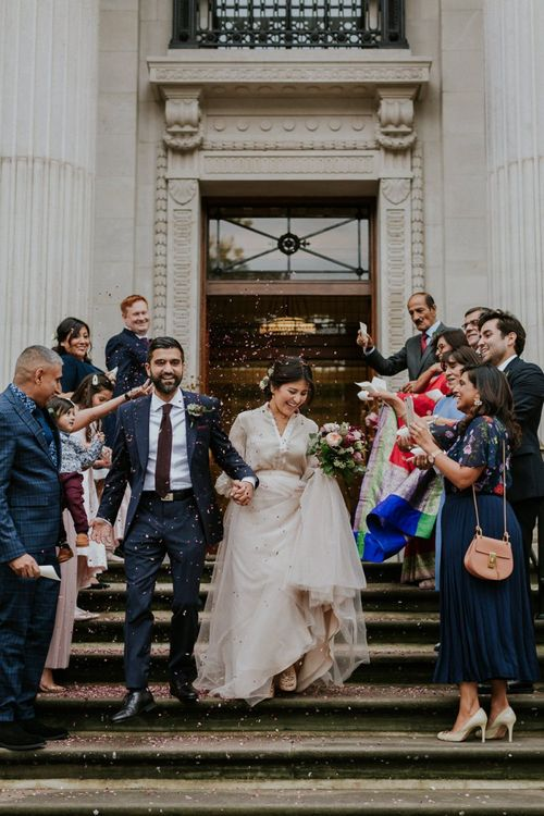 Bride in tulle skirt separates and groom in navy suit at town hall wedding