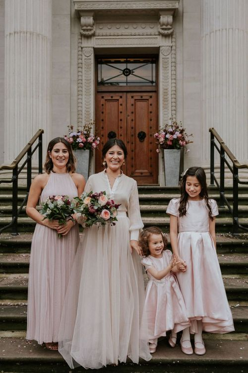 Bride and bridesmaid standing on the steps at Old Marylebone Town Hall