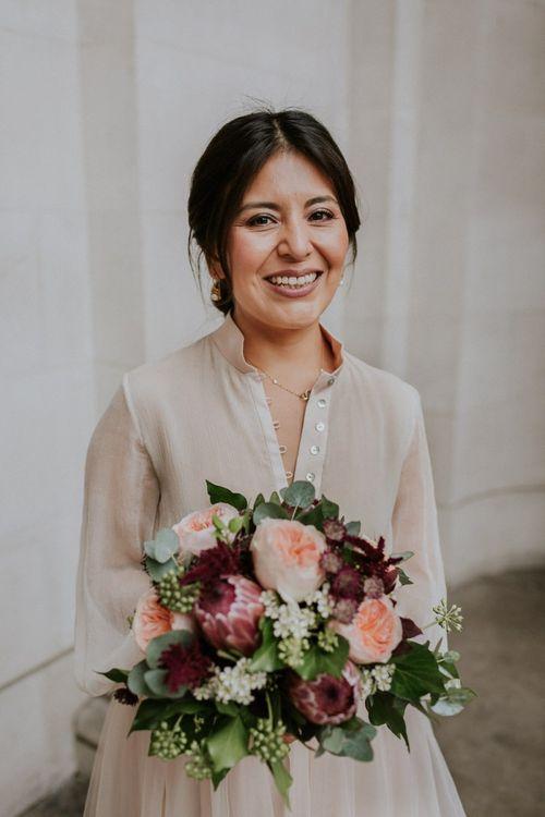 Bride holding a david austin rose and protea wedding bouquet