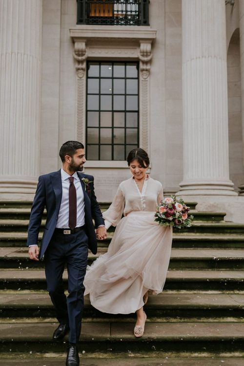 Bride and groom walking down the steps at The Old Marylebone Town Hall in a tulle skirt and navy suit