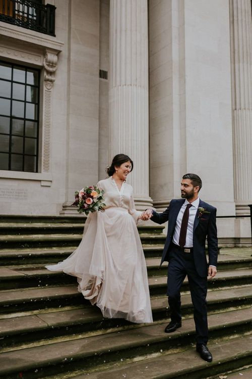 Groom helping his bride down the Old Marylebone Town Hall steps in her tulle skirt