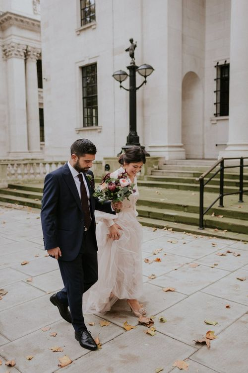 Bride and groom walking through London with autumn leaves on the floor