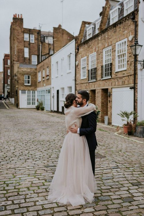 Bride and groom embracing in London Streets