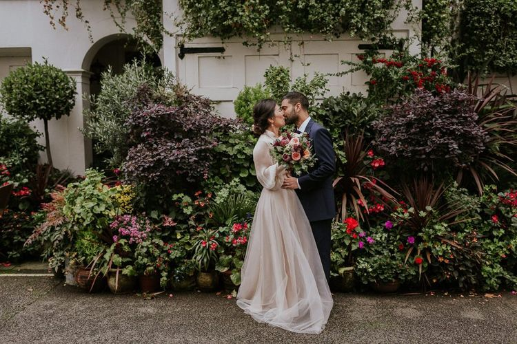 Bride and groom portraits next to some plants by Maja Tsolo Photography