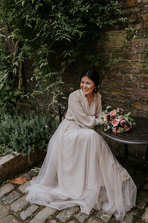 Bride sitting at a table in a tulle skirt