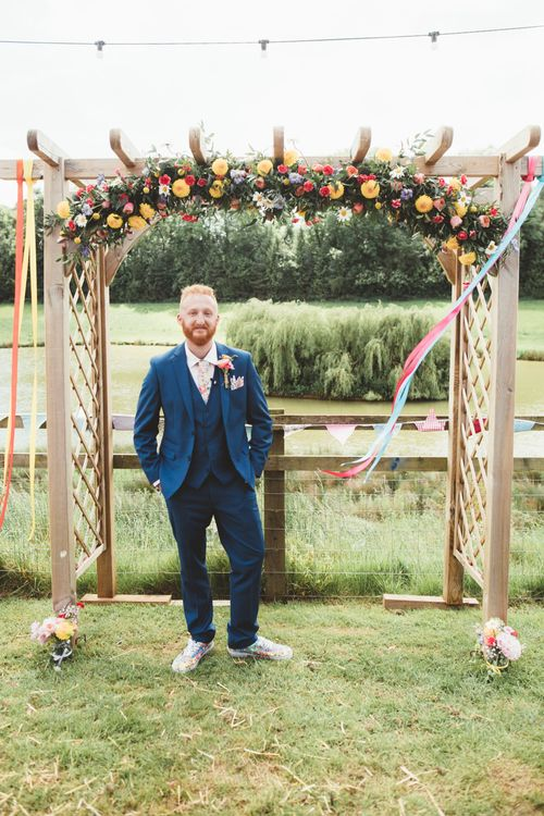 Groom at the Flower Covered Altar in Navy Suit | Bright Festival Themed Outdoor Ceremony & Tipi Weeding |  Maryanne Weddings | Framed Beauty Film