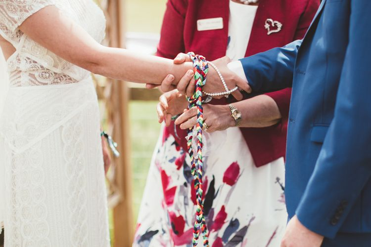 Hand Fastening Ceremony | Bride in Lace Watters Gown & Colourful Flower Crown | Groom in Navy Suit | Bright Festival Themed Outdoor Ceremony & Tipi Weeding |  Maryanne Weddings | Framed Beauty Film