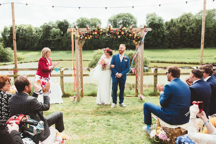Wedding Ceremony | Bride in Lace Watters Gown & Colourful Flower Crown | Groom in Navy Suit | Bright Festival Themed Outdoor Ceremony & Tipi Weeding |  Maryanne Weddings | Framed Beauty Film