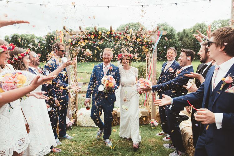 Confetti Exit | Bride in Lace Watters Gown & Colourful Flower Crown | Groom in Navy Suit | Bright Festival Themed Outdoor Ceremony & Tipi Weeding |  Maryanne Weddings | Framed Beauty Film