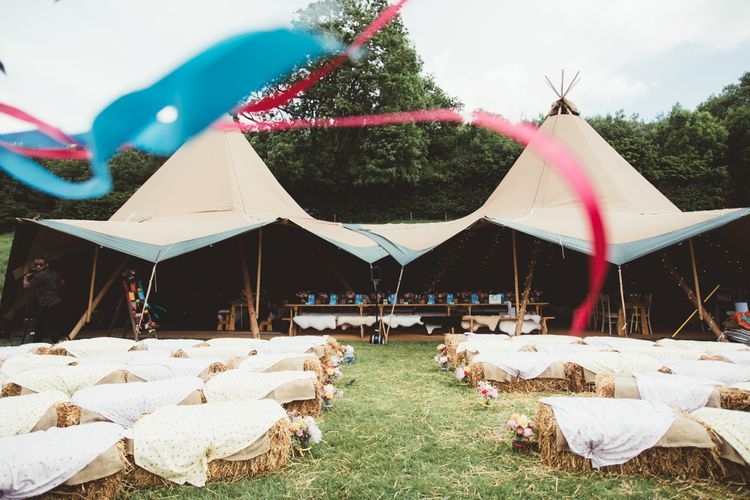 Hay Bale Ceremony Seating | Bride in Lace Watters Gown & Colourful Flower Crown | Groom in Navy Suit | Bright Festival Themed Outdoor Ceremony & Tipi Weeding |  Maryanne Weddings | Framed Beauty Film