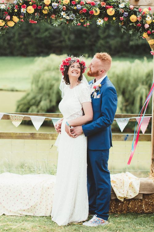 Bride in Lace Watters Gown & Colourful Flower Crown | Groom in Navy Suit | Bright Festival Themed Outdoor Ceremony & Tipi Weeding |  Maryanne Weddings | Framed Beauty Film