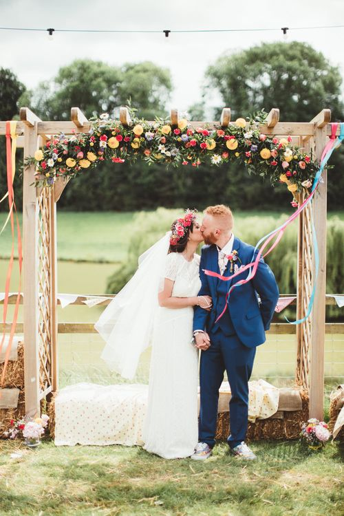 Flower Covered Arbour | Bride in Lace Watters Gown & Colourful Flower Crown | Groom in Navy Suit | Bright Festival Themed Outdoor Ceremony & Tipi Weeding |  Maryanne Weddings | Framed Beauty Film