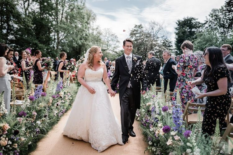 Bride in Lace Sophia Tolli Wedding Dress and Groom in Traditional Tails Walking up the Aisle as Husband and Wife