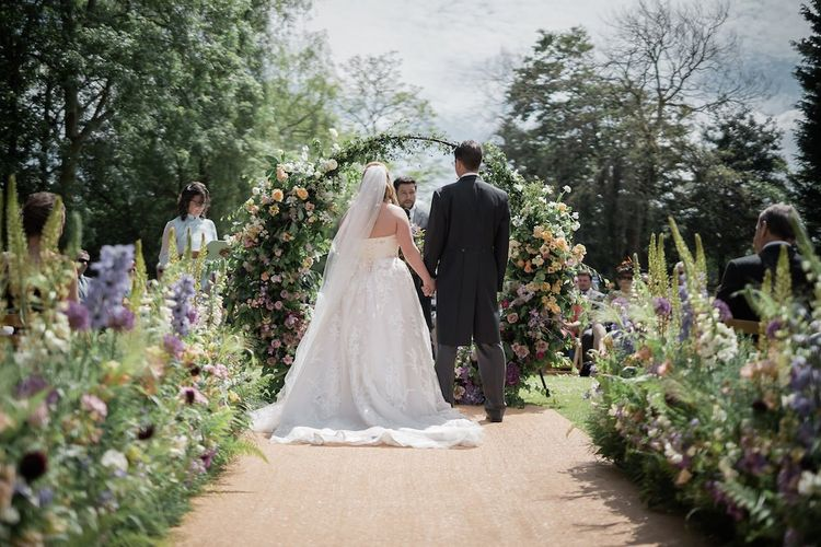 Bride in Lace Sophia Tolli Wedding Dress and Groom in Traditional Tails Exchanging Vows During the Outdoor Wedding Ceremony