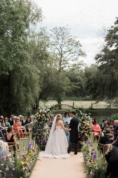 Outdoor Wedding Ceremony with Bride in Lace Sophia Tolli Wedding Dress and Groom in a Morning Suit
