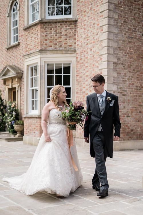 Bride in Lace Sophia Tolli Wedding Dress and Groom in Traditional Tails Walking Together