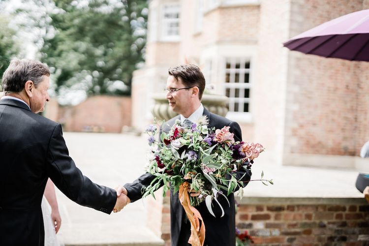 Groom in Traditional Morning Suit Holding the Brides Oversized Wedding Bouquet