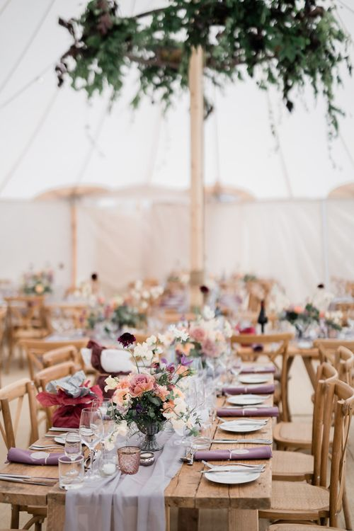 Marquee Wedding Reception Decor with Wooden Tables and Floral Centrepieces