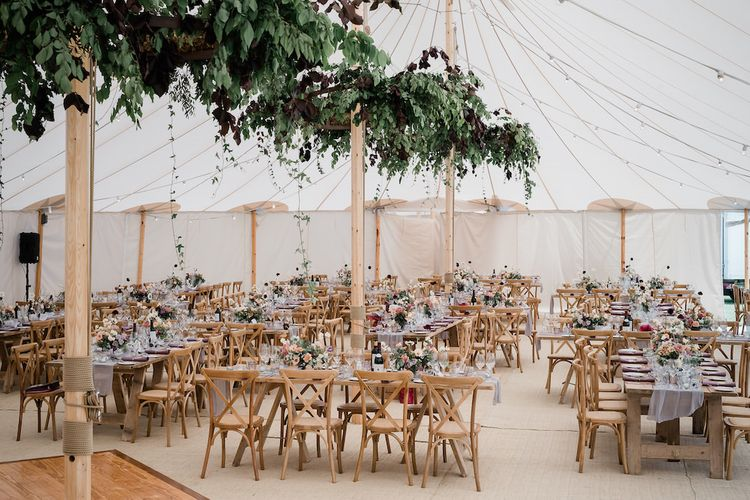 Marquee Wedding Reception with Hanging Greenery and Floral Arrangements on the Tables