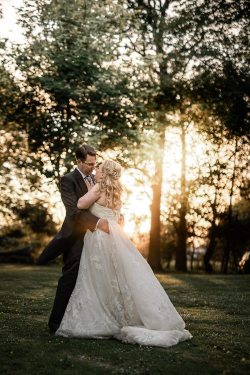 Bride in Lace Sophia Tolli Wedding Dress and Groom in Traditional Tails Embracing at Sunset