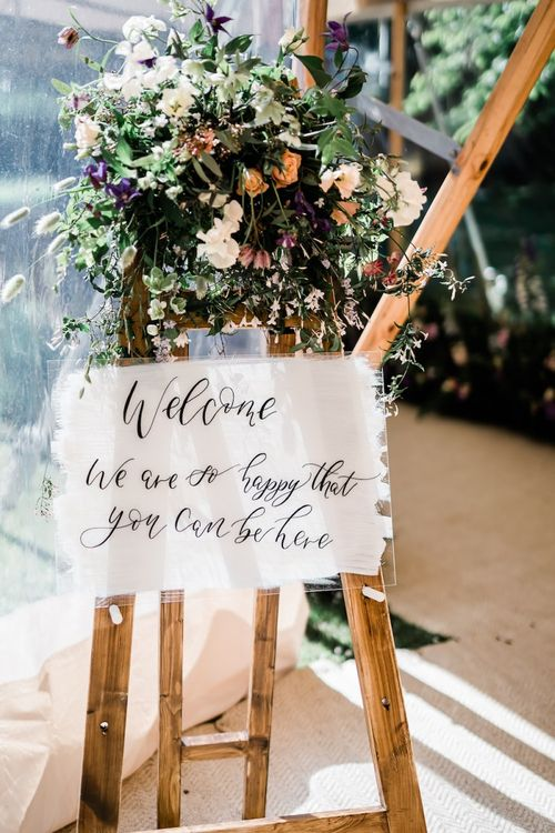 Acrylic Wedding Welcome Sign on a Wooden Easel Decorated with Flowers