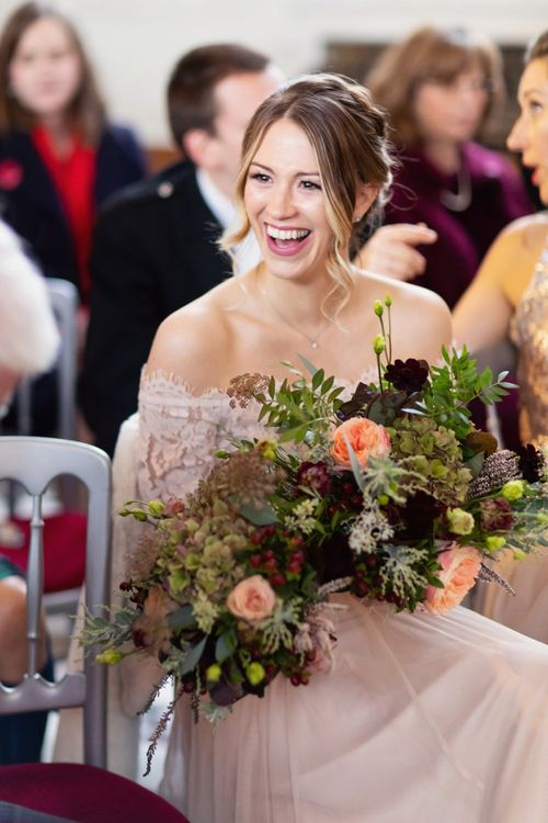 Laughing Bridesmaids in Pink Bardot Monsoon Wedding Dress Holding Deep Red and Green Winter Bouquet