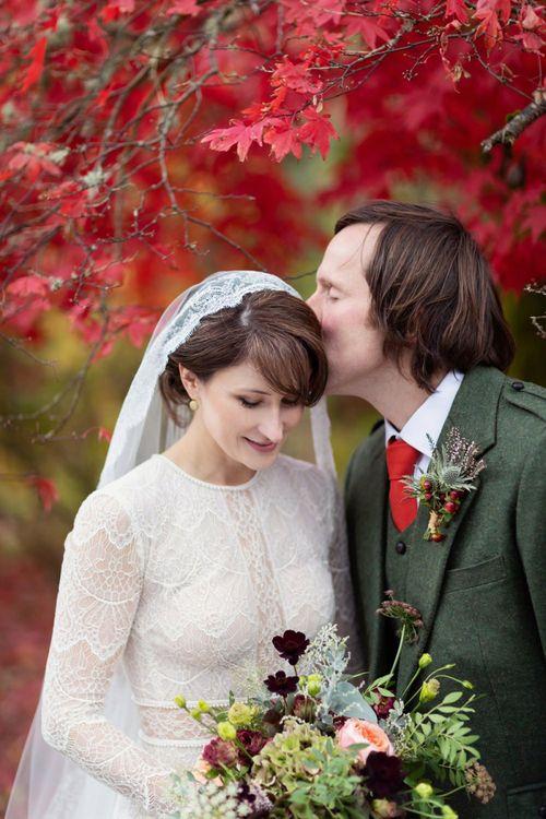 Groom in Traditional Tartan Kilt Kissing Brides Forehead in Lace Lihi Hod Sophia Wedding Dress