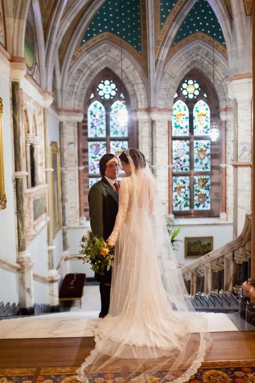 Bride in Delicate Lace Lihi Hod Sophia Wedding Dress with Long Sleeves and Groom in Traditional Tartan Kilt Standing in the Grand Hall of Mount Stuart in Scotland