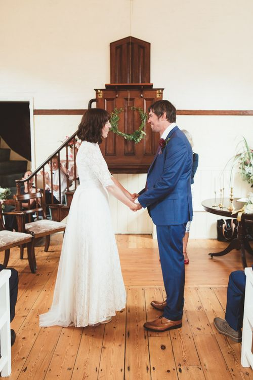 Bride in Lace Wedding Dress from Hope & Harlequin and Groom in Navy Hugo Boss Suit at the Altar
