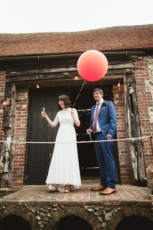 Bride in Lace Wedding Dress from Hope & Harlequin and Groom in Navy Hugo Boss Suit  Entering Drinks Reception with Giant Balloon