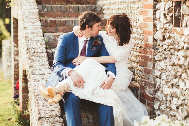 Bride in Lace Wedding Dress from Hope & Harlequin and Groom in Navy Hugo Boss Suit  Sitting on Steps