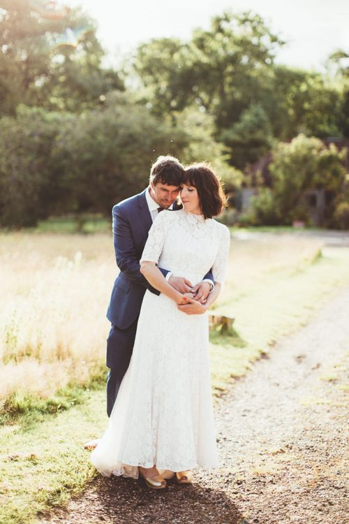 Bride in Lace Wedding Dress from Hope & Harlequin and Groom in Navy Hugo Boss Suit Embracing