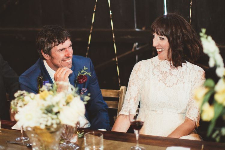 Bride in Lace Wedding Dress from Hope & Harlequin and Groom in Navy Hugo Boss Suit  Laughing  at  the Top Table