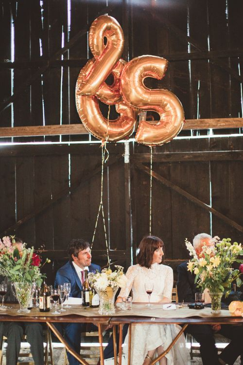Bride in Lace Wedding Dress from Hope & Harlequin and Groom in Navy Hugo Boss Suit Sitting at the Top Table with Copper Foil Balloons