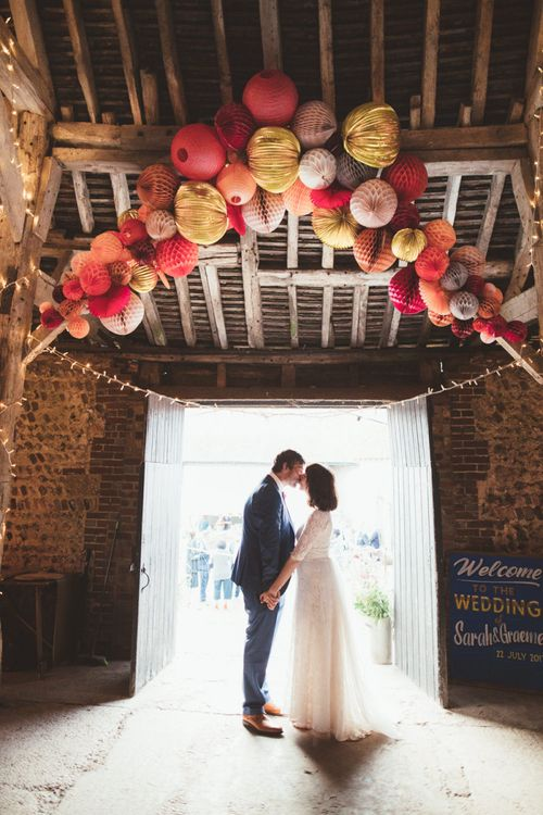 Bride in Lace Wedding Dress from Hope & Harlequin and Groom in Navy Hugo Boss Suit Standing under Pom Pom Wedding Decor