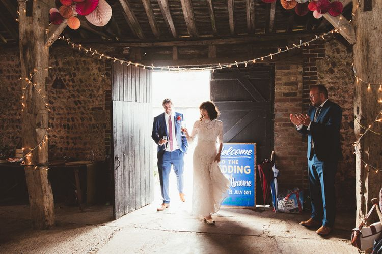 Bride in Lace Wedding Dress from Hope & Harlequin and Groom in Navy Hugo Boss Suit Entering Barn Reception