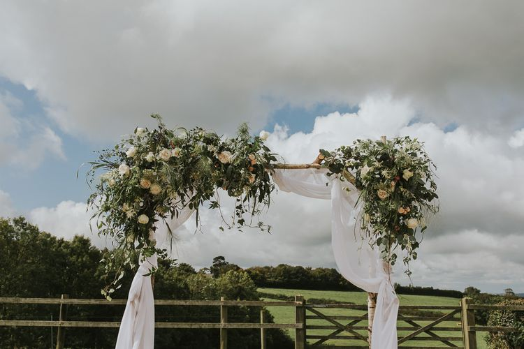 Floral Ceremony Arch With Drapes // Scottish Wedding With Ceilidh At Axnoller Dorset With Bohemian Styling Outdoor Wedding Ceremony With Images From Paul Underhill Dorset Wedding Photographer