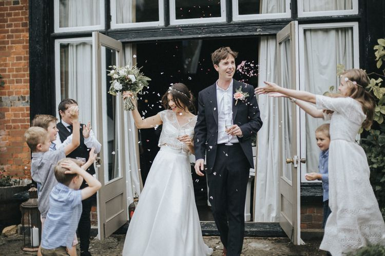 Confetti Exit | Bride in Suzanne Neville Separates | Groom in Gieves and Hawkes Suit | Intimate Wedding at The Olde Bell Pub, Berkshire | Revival Rooms Floral Design, Decor & Styling | Grace Elizabeth Photo & Film