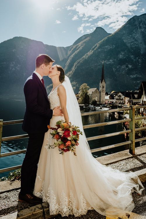 Bride and Groom Kissing with Hallstatt, Austria Scenery in the Background