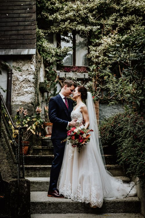 Bride in Lace Angelic Bridal Gown and Groom in Navy Suit Embracing