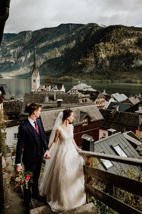 Bride and Groom Holding Hands with Rooftop Scenery of Hallstatt in Austria as the Backdrop