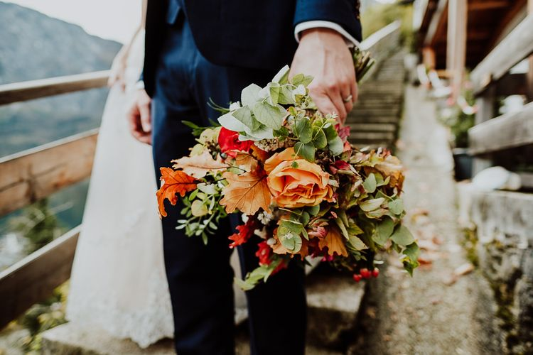 Groom Golding the Autumnal Orange Flower and Green Leaf Wedding Bouquet