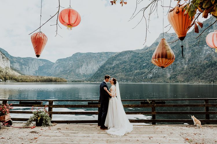 Bride and Groom Portrait By The Waters Edge with Hanging Lanterns in The Tree