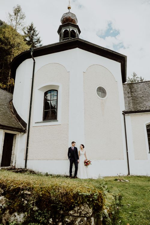 Bride and Groom Standing by The Wall of a Church in Hallstatt, Austria