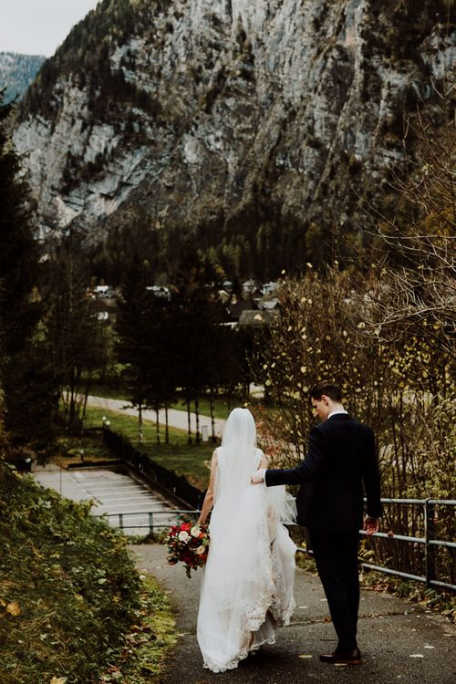 Groom Holding Up His Brides Wedding Dress as They Walk Down Some Steps