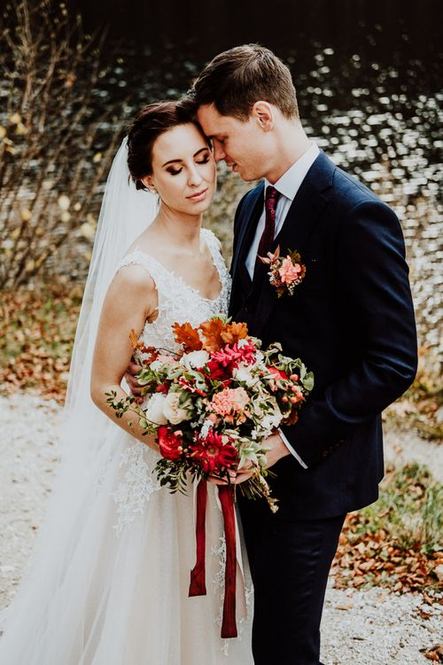 Bride and Groom Embracing Holding a Red, Orange and Green Wedding Bouquet with Ribbons